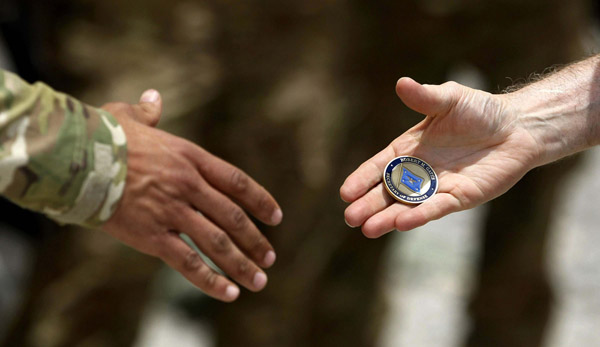 U.S. Secretary of Defense Robert Gates hands a challenge coin to a solider at FOB Walton in Afghanistan