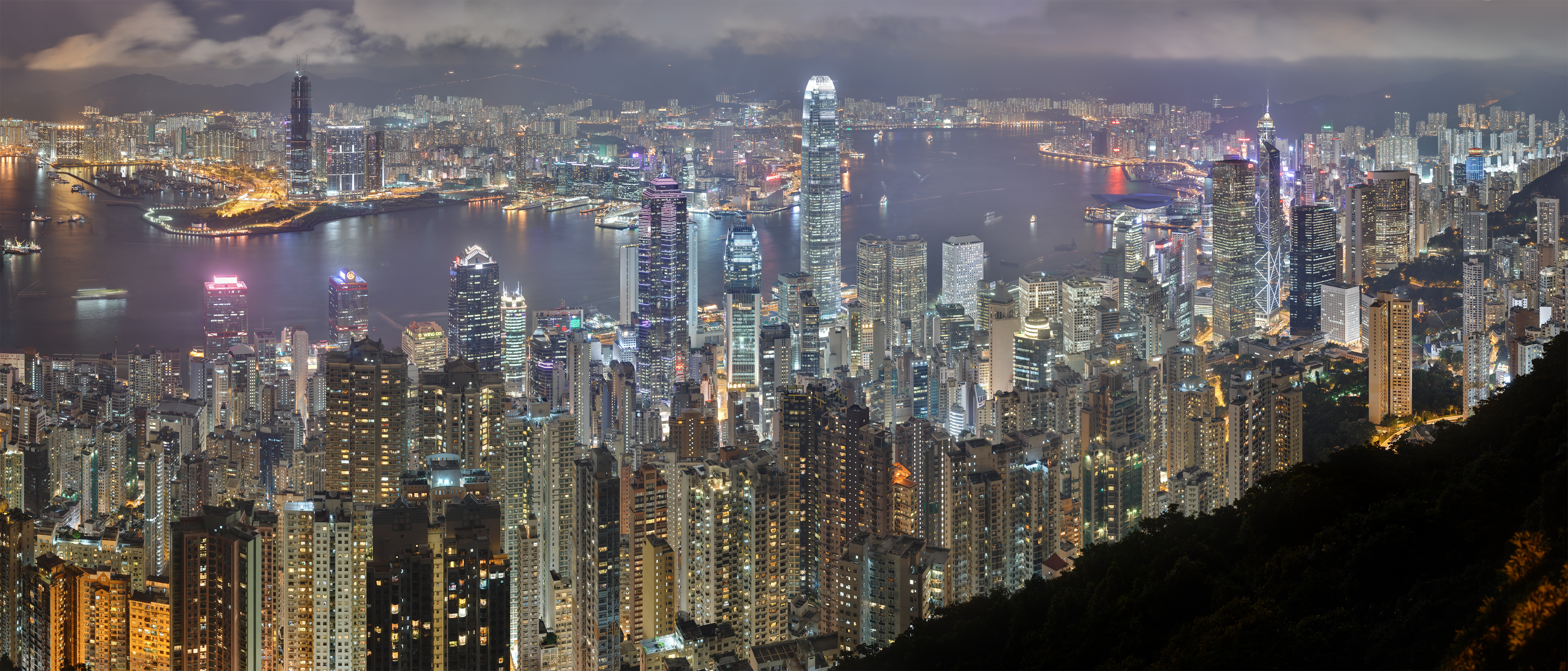 Victoria Harbour and the Hong Kong skyline at night from the hills behind the city by Base64, retouched by CarolSpears (CC BY-SA 3.0)